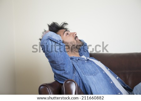 Side view of a tired or unhappy Asian man sitting on sofa holding his head.