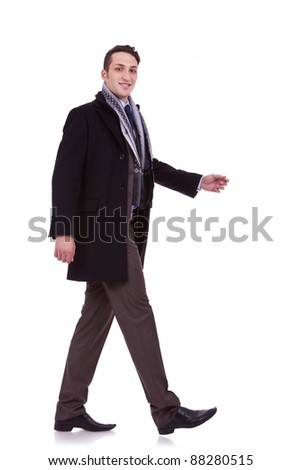 side view of a walking business man, looking to the camera, on white background