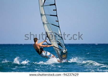 Side view of a windsurfer passing by