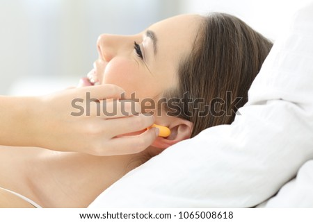 Side view of a woman hand covering ears using plugs on the bed