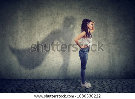 Side view of a woman imagining to be a super hero looking aspired.  #1080530222