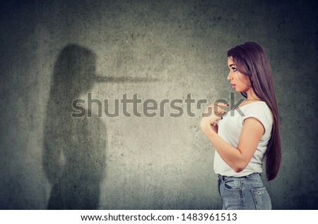 Side view of a woman pointing at herself looking at a shadow with long nose of a liar. Сток-фото ©