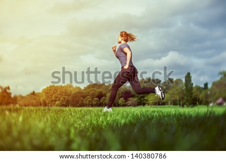 Side view of a woman running on the grass