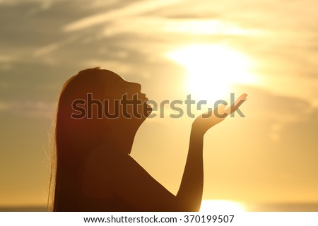 Side view of a woman silhouette kissing the sun on the beach at sunset