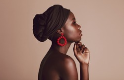 Side view of a woman wearing black turban against beige background. African female model with beautiful skin posing in studio.