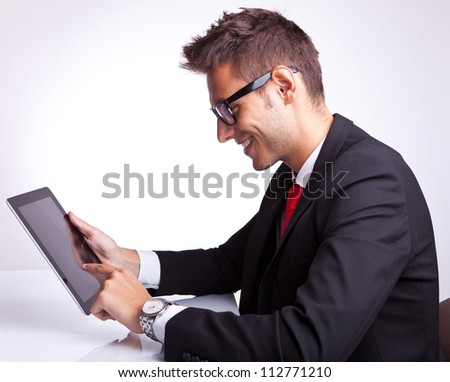 side view of a young business man browsing on his tablet pad