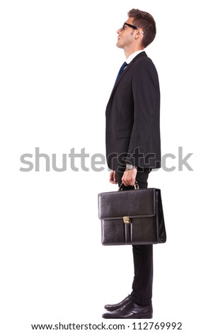 side view of a young business man or student looking up - full body picture