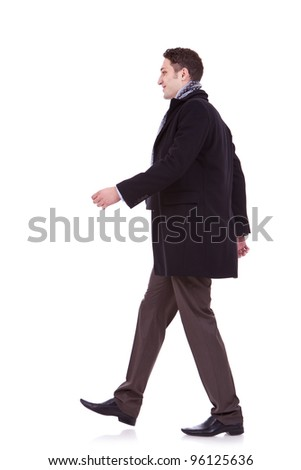 side view of a young business man walking forward on white background - stock photo