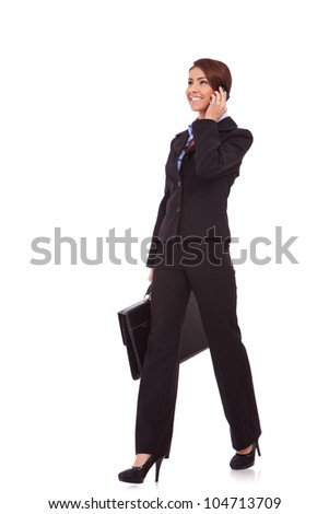 side view of a young business woman talking on the phone and holding a brief case while walking on white background