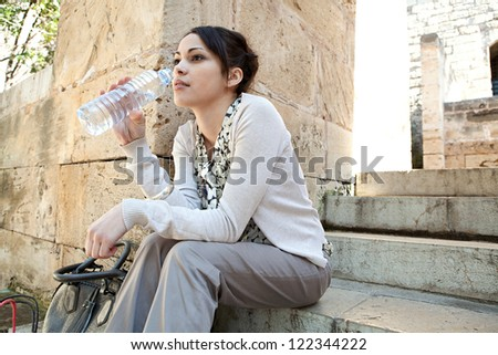 Side view of a young businesswoman sitting on a park steps drinking water from a plastic blue bottle.