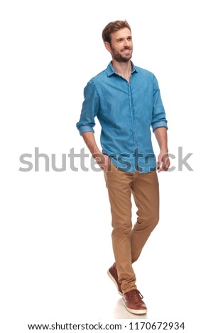 side view of a young casual man walking and looking away on white background #1170672934