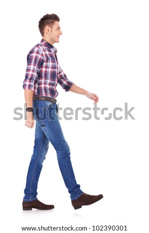 side view of a young casual man walking forward, on white background