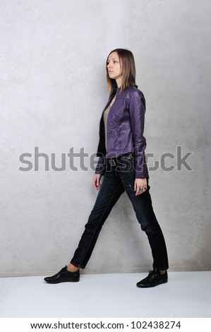 Side view of a young casual woman on grey background
