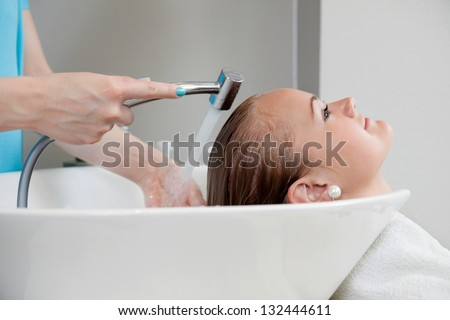 Side view of a young Caucasian woman getting her hair washed at beauty salon