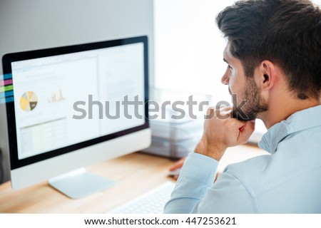 Side view of a young confident handsome businessman working on laptop in office #447253621