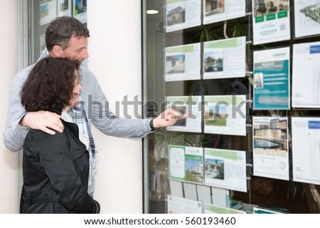 Side view of a young couple looking at window display at real estate office #560193460