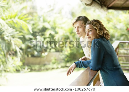Side view of a young couple on vacations, leaning on a balcony's veranda and looking at a tropical garden. - stock photo