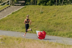 Side view of a young fitness woman running using red resistance parachute tied to her waist