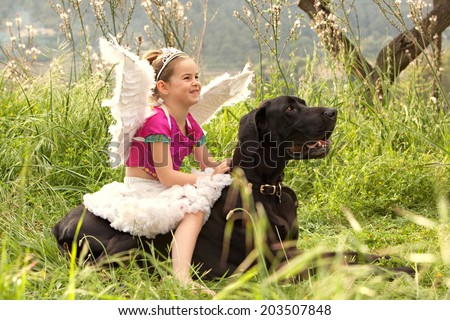 Side view of a young girl wearing a pink fancy dress with wings, sitting on her dogs back enjoying a sunny holiday in a green park field, smiling outdoors. Active family with animal pets, lifestyle.