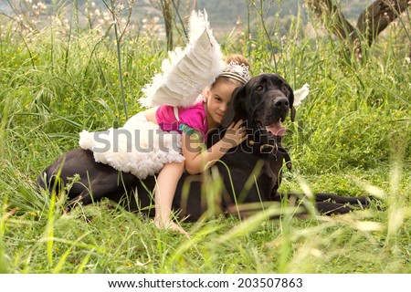 Side view of a young girl wearing a pink fancy dress with wings, sitting on her dogs back enjoying a sunny holiday in a green park field, hugging him outdoors. Active family with pets, lifestyle.