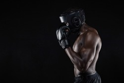 Side view of a young male boxer in a fighting stance on black background. African male boxer blocking his face with gloves.