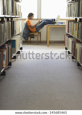 Side view of a young male college student doing homework in the library