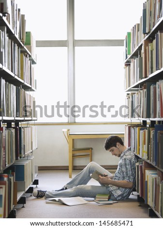 Side view of a young male college student reading in the library