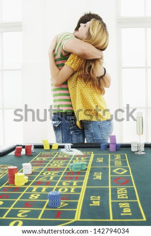Side view of a young man hugging woman at roulette table