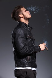 side view of a young man in leather jacket smoking and blowing the smoke