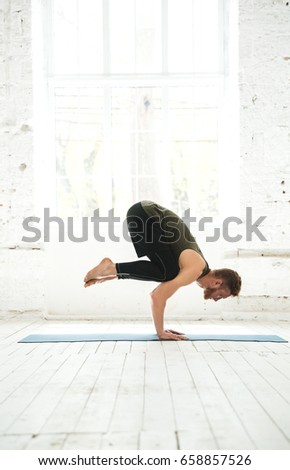 Side view of a young man practicing advanced yoga indoors