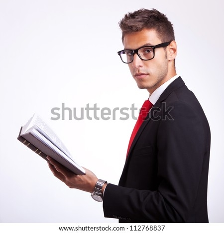 side view of a young student holding a book and looking at the camera