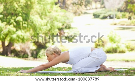 Side view of a young woman doing stretches in the park