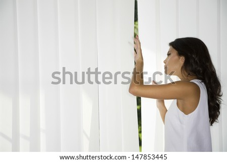 Side view of a young woman looking trough curtains