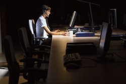 Side view of a young woman working on computer in dark office