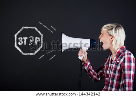 Side view of a young woman yelling into the megaphone against black background