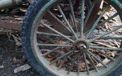 side view of abandoned wagon metal wheel outside