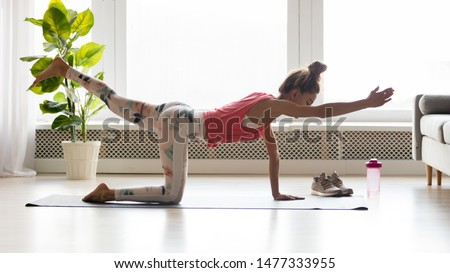 Side view of active fit young woman in sportswear standing and raising opposite knees and hands, doing donkey kick balance exercise, practicing yoga, strengthen full body, healthy daily habits concept
