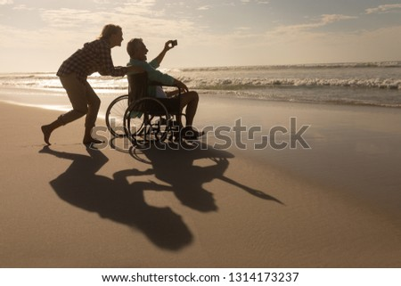 Side view of active senior couple taking selfie with mobile phone on the beach