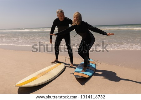 Side view of active senior surfer couple standing with surfboard on the beach #1314116732