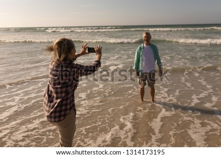 Side view of active senior woman clicking photo of senior man on the beach