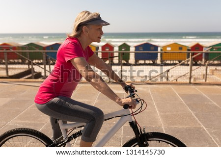 Side view of active senior woman riding a bicycle on a promenade at beach #1314145730