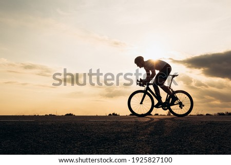 Side view of active sportsman in protective helmet riding bike among nature during sunset. Muscular guy in activewear cycling on paved road. Foto stock ©