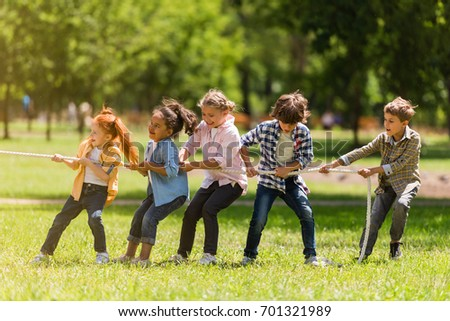 side view of adorable multiethnic kids pulling rope in park