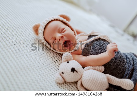 Side view of adorable newborn baby wrapped in wool scarf and with little cap on head while lying next to toy on fur blanket.