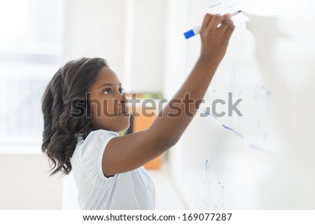 Side view of African American girl solving math problem on whiteboard in classroom - stock photo