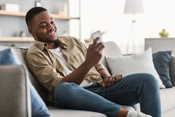Side View Of African American Guy Using Smartphone Browsing Internet Sitting On Couch At Home. Black Man Texting On Cellphone Or Using New Application On Mobile Phone Indoors