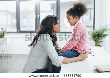 side view of african american mother talking with her daughter indoors