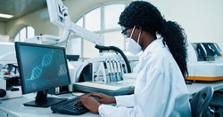 Side view of African American young female medical expert sitting at workplace in lab working typing on computer looking at molecular structure. Scientist using computer in his modern laboratory