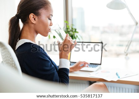 Side view of African business woman in dress sitting by the table in office and drinking water