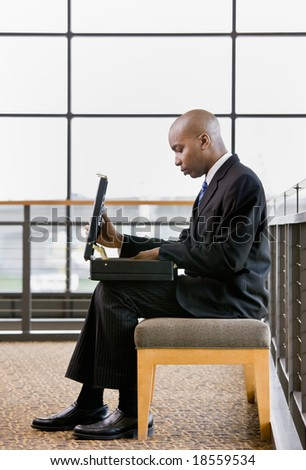 Side view of African businessman looking in briefcase in office lobby